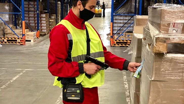 Warehouse worker in a red shirt scanning a barcode while wearing a mask