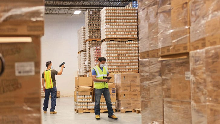 2 Warehouse workers using the MC9300 safely distanced in a warehouse