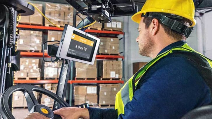 Forklift driver looking at screen with hardhat in a warehouse